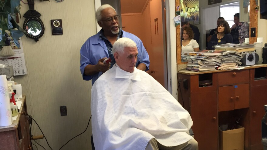 Indiana Gov. Mike Pence, the GOP vice presidential nominee, gets his hair trimmed by barber Henry Jones in Norristown, Pa.