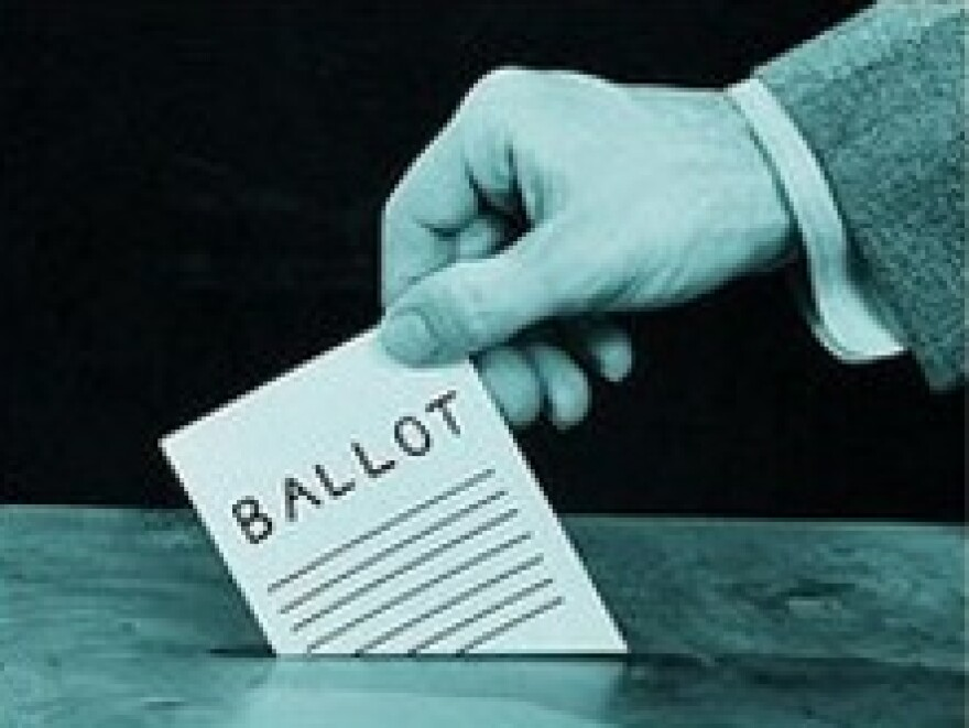 Hand dropping ballot into a box.