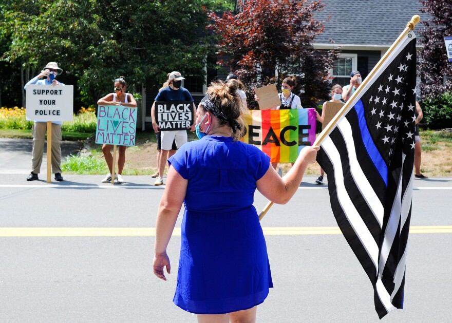 A rally between who are for and against thin blue line flags in Hingham, Mass., on Tuesday. Some see the flag as a proud tribute to police officers, while others denounce it as a racist symbol.
