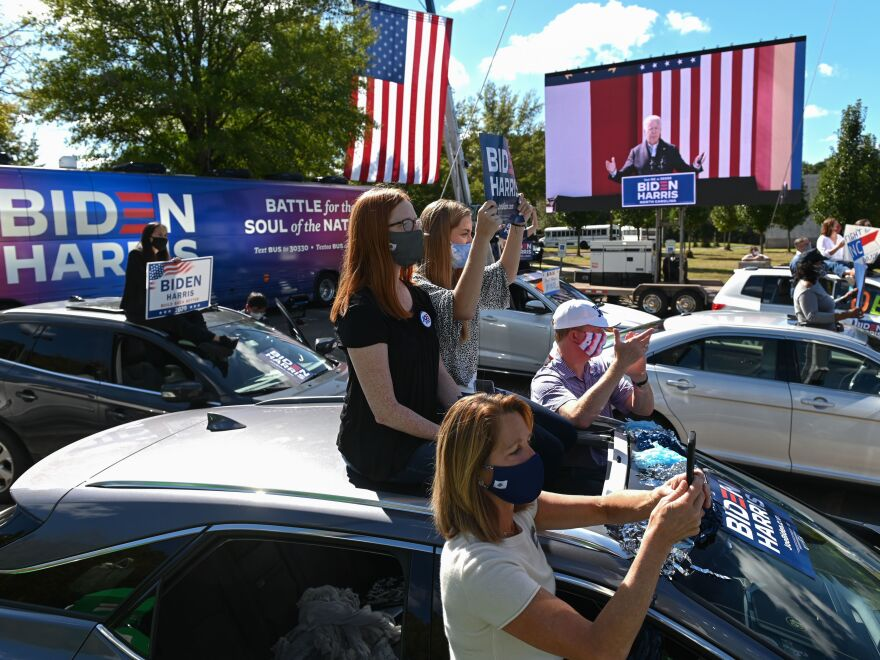 Supporters of Democratic presidential nominee Joe Biden sit on top of their vehicles as they listen to him speak at Riverside High School in Durham, N.C., on Sunday afternoon.