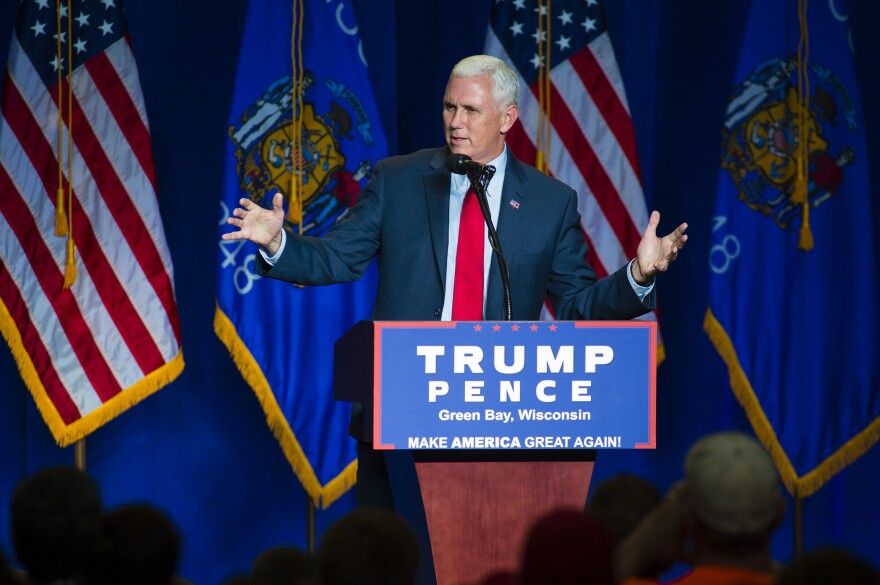 Mike Pence greets the crowd before introducing Donald Trump at a campaign rally in 2016 in Green Bay, Wis.