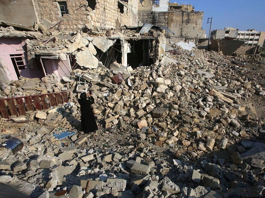 Kefa Jawish takes pictures of the rubble as she heads with her husband to check their house for the first time in four years in Aleppo's northeastern Haydariya neighborhood on Dec. 4.