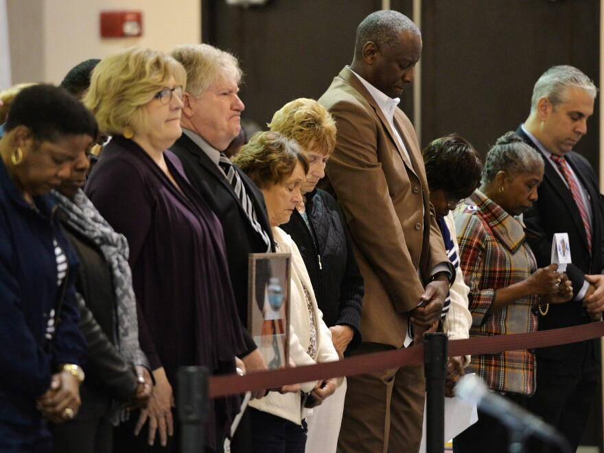 Family members of the crew stand during a moment of silence for those lost on the El Faro ship in February.