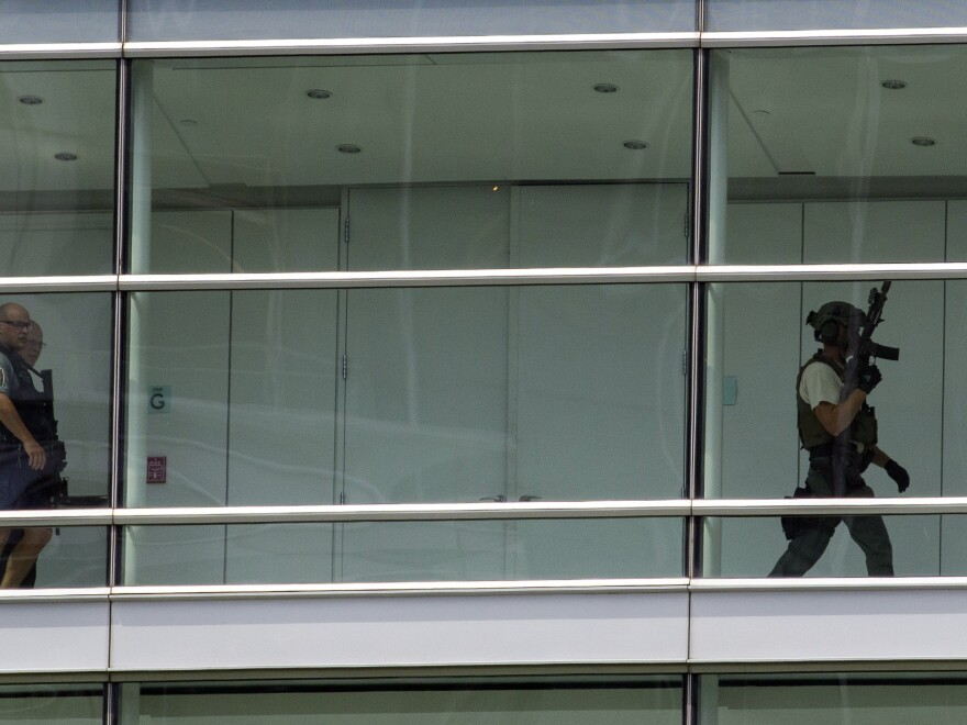 Law enforcement officers search one of the buildings that house Gannett and <em>USA Today</em> on Wednesday. No gunman was found.