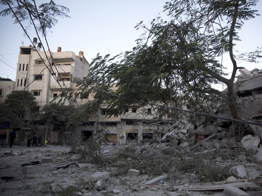 Palestinians check on Tuesday the damage of a building destroyed by Israeli airstrikes in Gaza City.