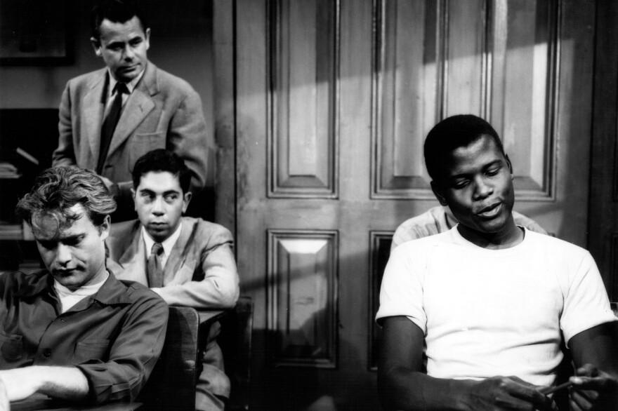 Sidney Poitier (right) and Glenn Ford (standing) in the 1955 film <em>Blackboard Jungle. </em>