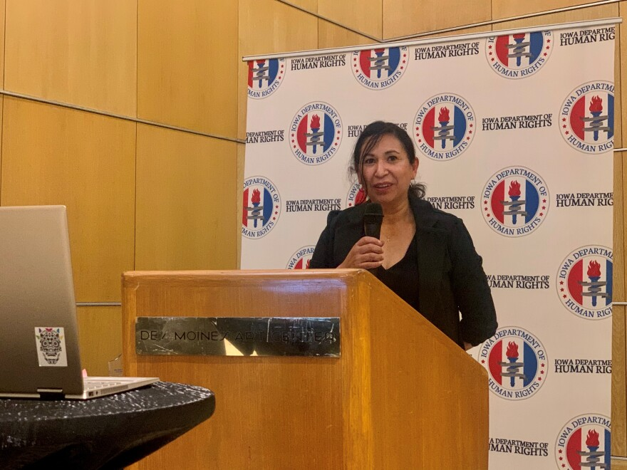 """A woman stands behind a podium with """"Iowa Department of Human Rights"""" behind her. She is holding a microphone."""
