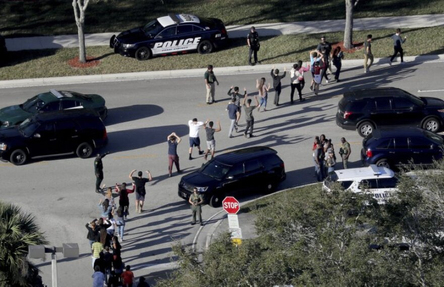 this Wednesday, Feb. 14, 2018 file photo, students hold their hands in the air as they are evacuated by police from Marjory Stoneman Douglas High School in Parkland, Fla.