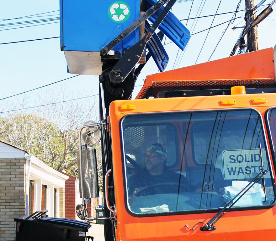 A St. Louis city refuse collector collects an alley container full of recycling.