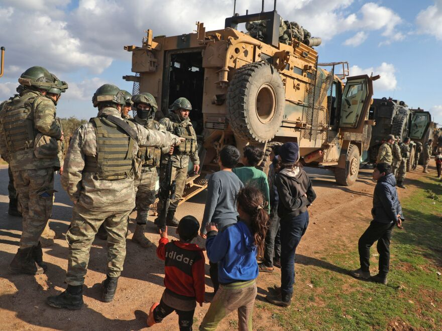 Displaced Syrian children speak with Turkish soldiers near the town of Batabu on the highway linking Idlib to the Syrian border crossing with Turkey on March 2.