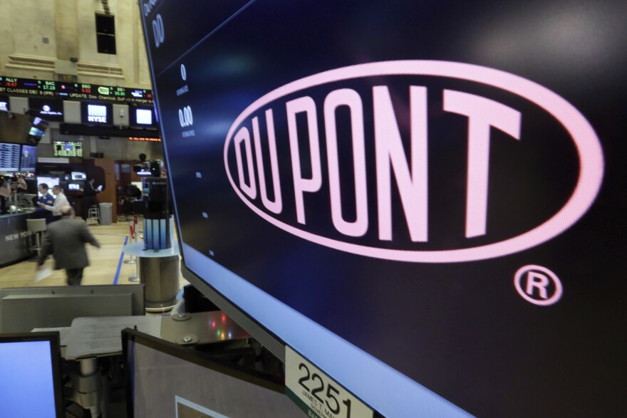 In this Dec. 9, 2015, file photo, the company name of Dupont appears above its trading post on the floor of the New York Stock Exchange.