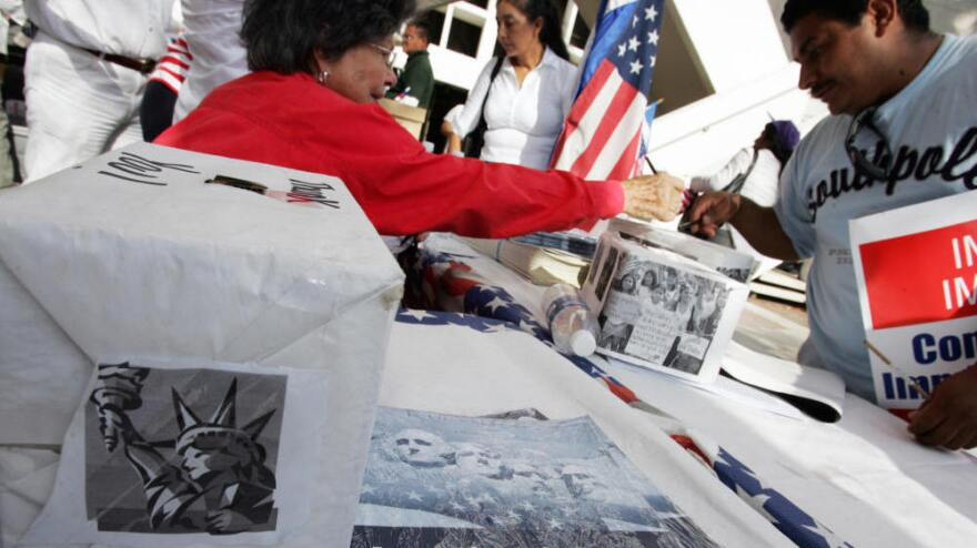 <p>An immigrant signs a voter registration information card at a booth set up at a rally in downtown Miami in 2007. If a new law is upheld, the time period groups have to turn in new voter registrations will be reduced from 10 days to two.</p>