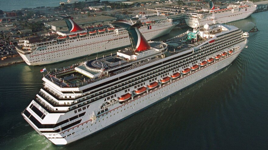 In a photo from 1999, the Carnival Cruise line Carnival Triumph, foreground, arrives in Miami. Measuring 893 feet in length, the ship has been adrift in the Gulf of Mexico for more than 24 hours, after a fire hit its engines.