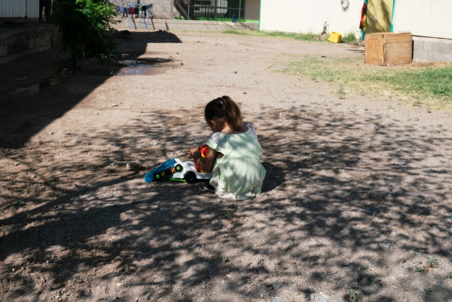 Tania and Joseph's 3-year-old daughter, Sofi, plays with a car in the shade at a shelter in Juárez, Mexico, last week.