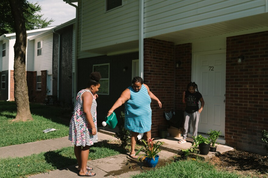 Talayla Feggins (left) and Tranese Feggins (right) help their mother, Harriet Feggins, water flowers at their home in west Atlanta. Harriet has shut off the power in some rooms and has hung blackout curtains to try to keep the house cool and her electric bill low.