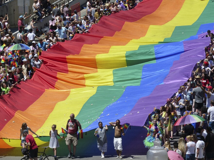 """Marchers raise a rainbow flag during the 2018 Pride parade in Salt Lake City. Late Tuesday, state regulators implemented a ban on """"conversion therapy"""" aimed at changing the sexual orientation or gender identity of LGBTQ young people."""