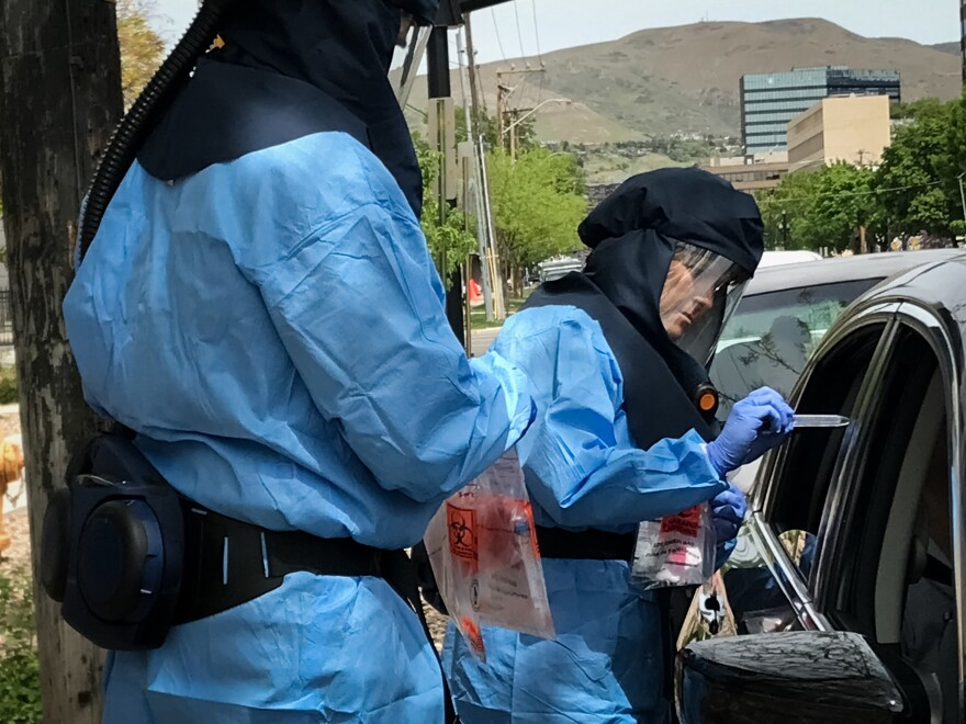 Wearing a protective suit, Lee Cherie Booth, a public health nurse with the Salt Lake County Public Health Department, reviews the name of a person she is about to test for the coronavirus.