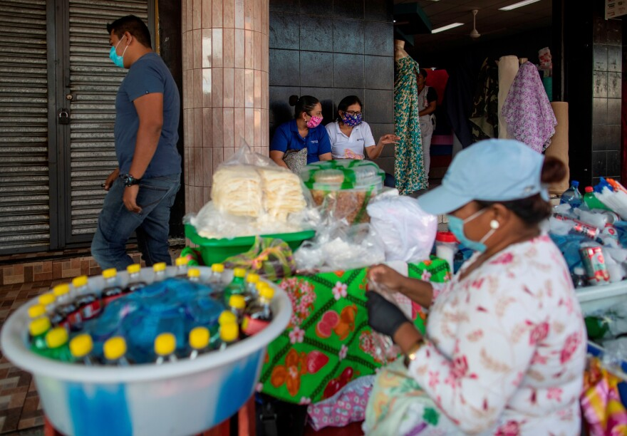 People wear face masks as a preventive measure against the spread of the new coronavirus, COVID-19 at a market in Managua, on April 16, 2020, a day after Nicaraguan President Daniel Ortega spoke of the coronavirus pandemic and announced there would be no quarantine or cessation of economic activity.