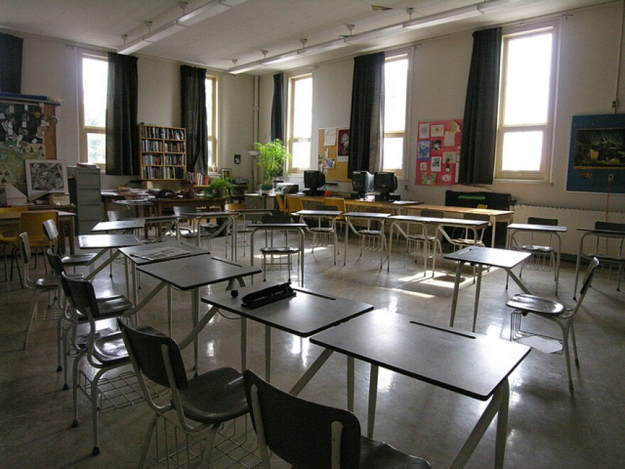 An empty classroom with desks arranged in a square.