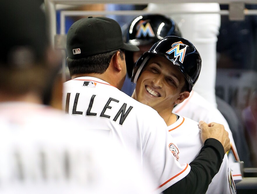 Adam Greenberg of the Miami Marlins hugs manager Ozzie Guillen after striking out against the New York Mets.