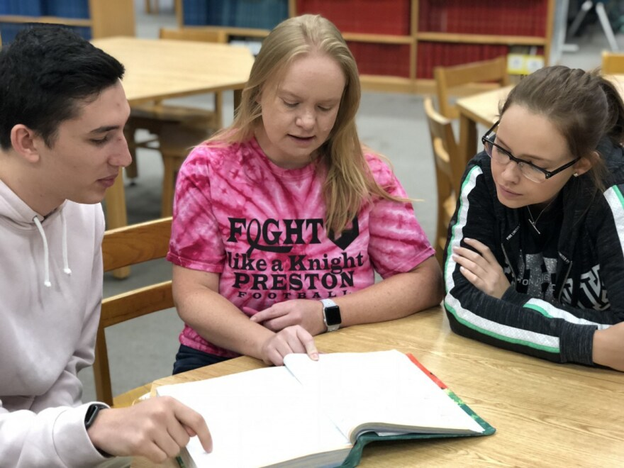 Henry Cerbone, left, and Abby Pletcher, right, seniors at Preston County High School, sit with their teacher Danielle Barker. Barker distributed the survey to her students.