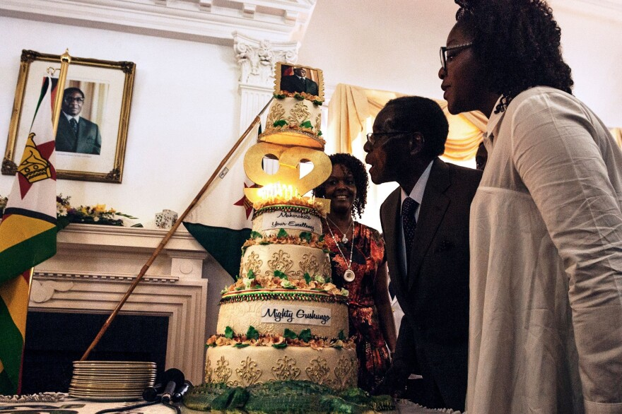 Zimbabwe President Robert Mugabe, flanked by his wife Grace Mugabe (left) and daughter Bona (right), blows candles on his cake during a surprise birthday party at the Statehouse in Harare, on Feb. 22. His birthday was Feb. 21; he held a massive celebration Saturday.