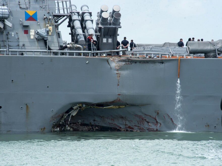 Damage to the port side is visible as the guided-missile destroyer USS John S. McCain steers toward Changi naval base in Singapore following a collision with the Alnic MC tanker on Monday.