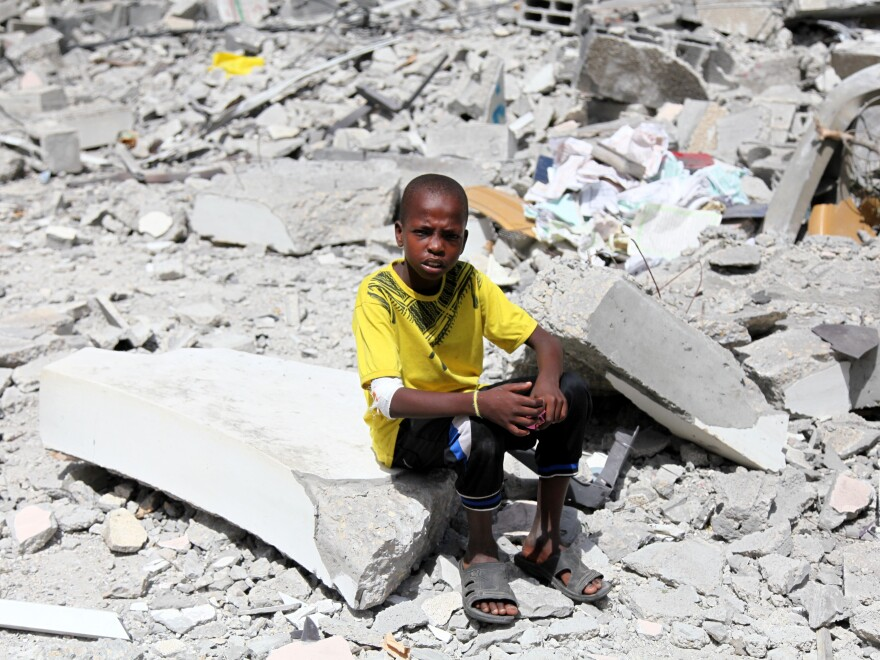 A Palestinian boy sits on the rubble of Al-Farouk mosque, which police said was destroyed in an Israeli airstrike, in Nuseirat in the central Gaza Strip on Saturday.