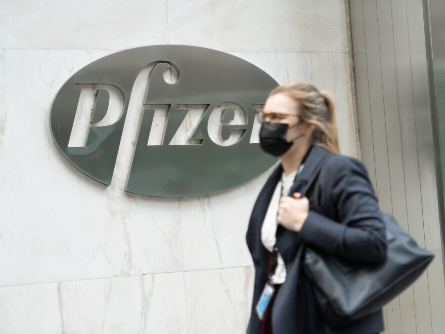 A woman wearing a face mask walks past a Pfizer's headquarters in New York.