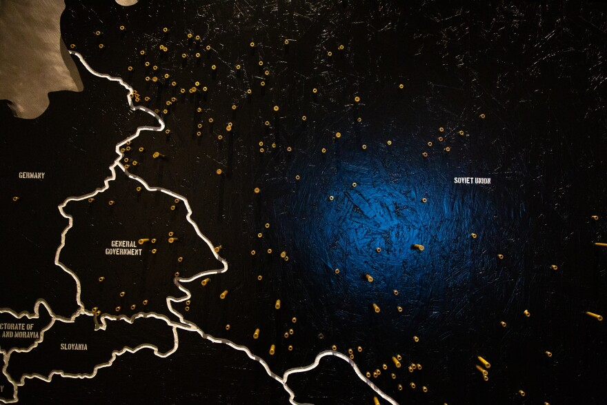Gold bullets stick out from a map on the wall, showing how many Jewish people were killed by shootings in the Soviet Union, General Government, and Germany.