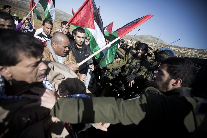 An Israeli soldier pushes Palestinian Cabinet member Ziad Abu Ain (left) during a protest in the village of Turmus Aya near the West Bank city of Ramallah, on Wednesday. Abu Ain died shortly after the protest in which witnesses said Israeli troops fired tear gas at him and dozens of Palestinians marchers. Witnesses also said Abu Ain was beaten by an Israeli soldier.