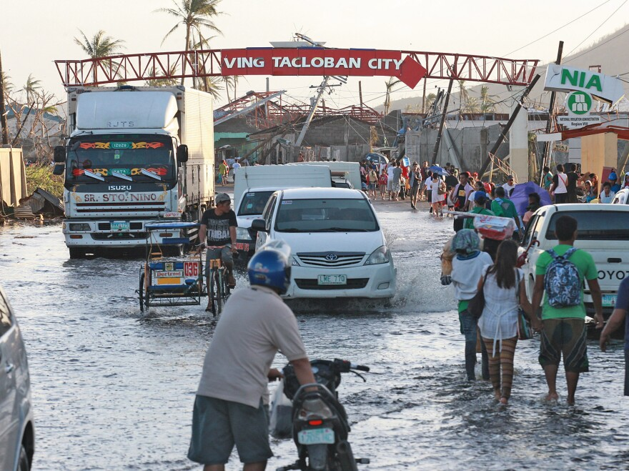 Residents wade through flood waters on Sunday in Tacloban City, Leyte, Philippines, in the aftermath of Typhoon Haiyan.