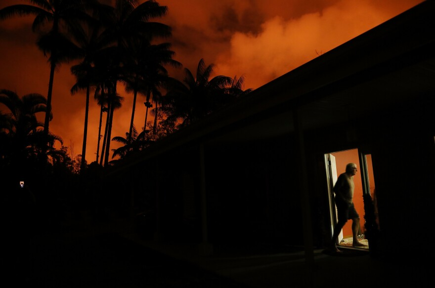 Bill Hubbard enters his home as lava illuminates the sky in Leilani Estates. Hubbard's home is about three blocks from the lava.