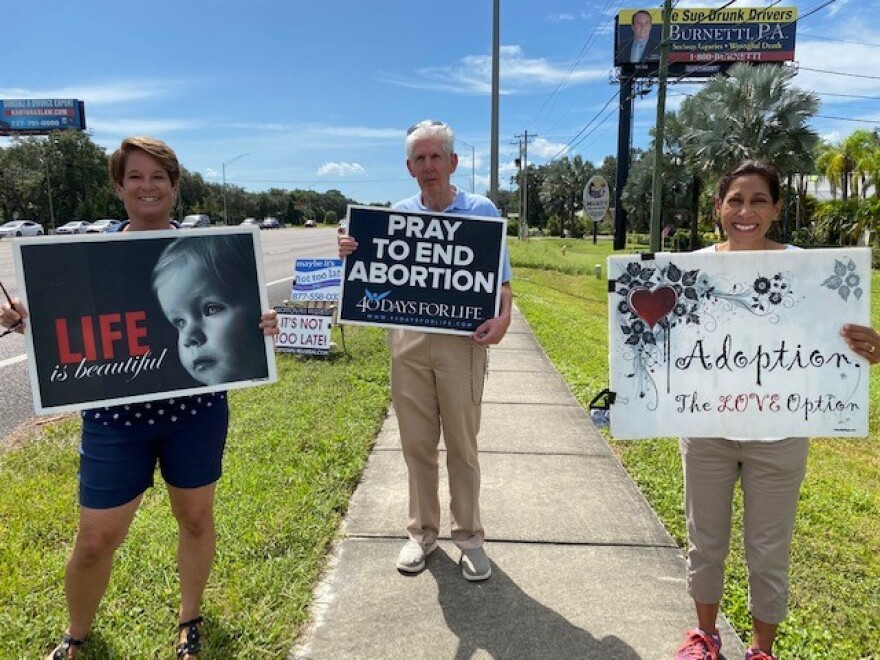 Three people standing on a sidewalk holding pro-life signs.