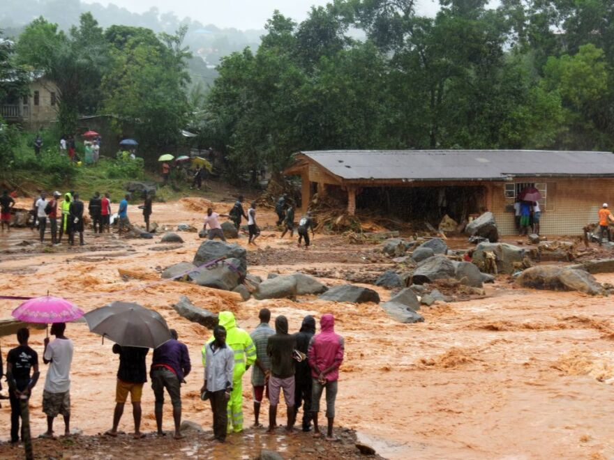 Floodwaters rage past a damaged building on the outskirts of Freetown on Monday, after mudslides struck near the capital of the west African state of Sierra Leone.