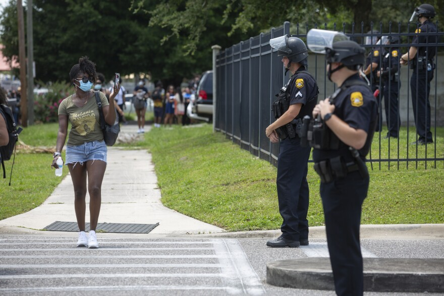 a woman wearing a mask at a Black Lives Matter Tampa protest points her cell one camera at Tampa Police Officers wearing riot gear.