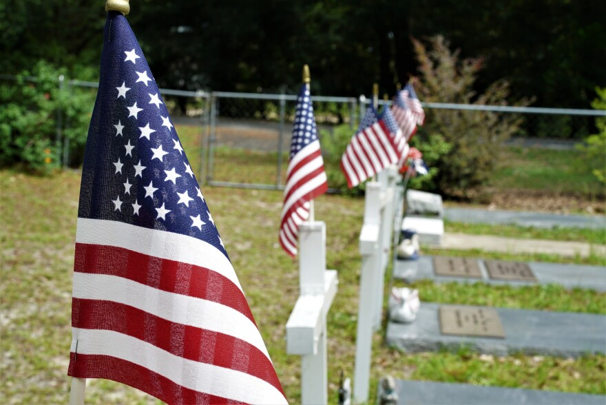 American Flags stick out from tombstone crosses inside the VFW cemetary.