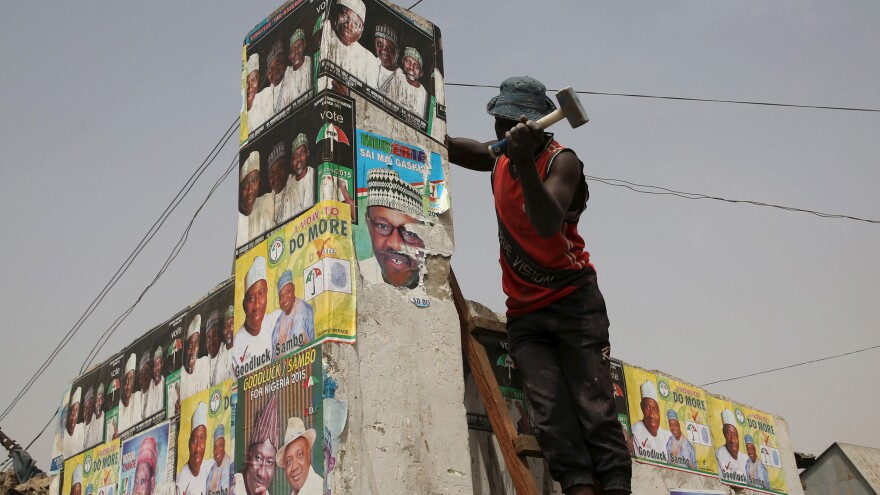 A man hammers a wall with elections posters at an open market in Kano, Nigeria, on Friday. The country is preparing for presidential elections on Saturday. President Goodluck Jonathan faces former military ruler Muhammadu Buhari and 13 other candidates in what is seen as the closest presidential race since the end of military rule in 1999.