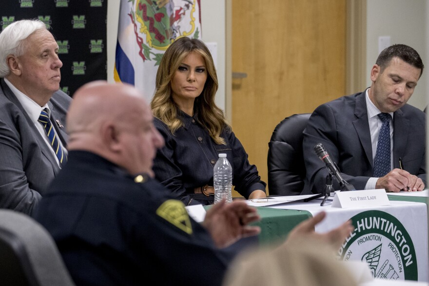 West Virginia Gov. Jim Justice, left, first lady Melania Trump, center, and Acting Homeland Security Secretary Kevin McAleenan, right, listen as Huntington Police Chief Hank Dial, speaks at Cabell-Huntington Health Center in Huntington, WVa., July 8, 2019
