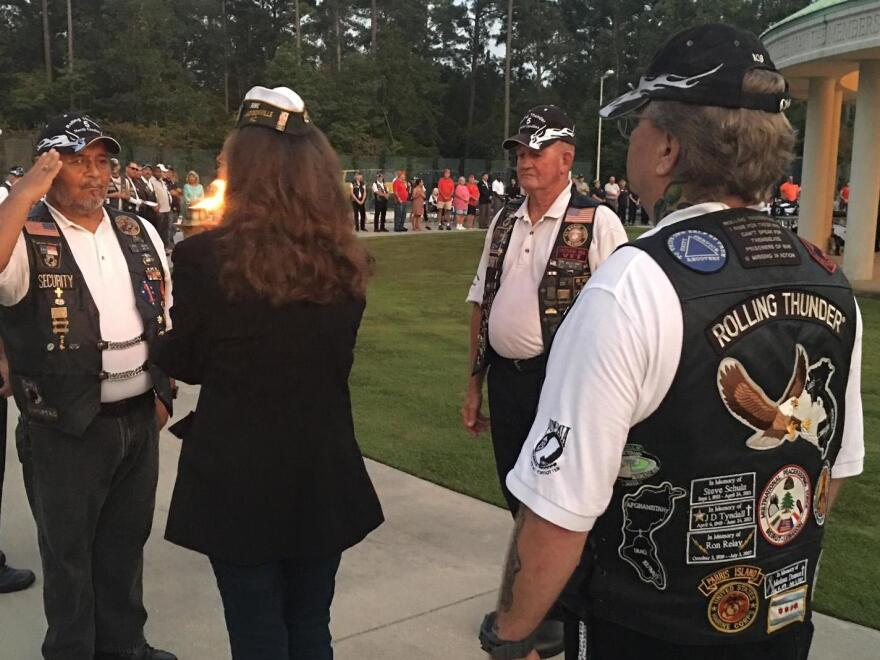 Members of the Jacksonville, N.C., Rolling Thunder chapter pass a flame during a ceremony honoring prisoners of war and troops missing in action.