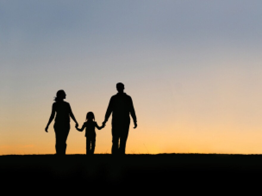 Silhouette of parents and child.