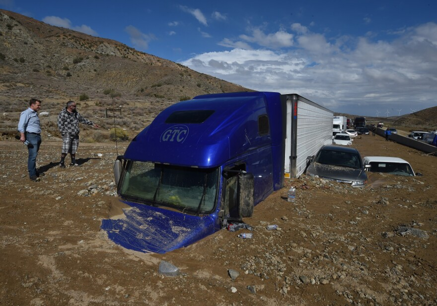 Reporters look at vehicles stuck on a road after being trapped by a mudslide on California Highway 58 in Mojave on Saturday.