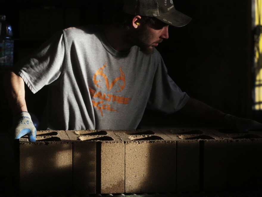 An employee moves cement blocks at the Cement Products Manufacturing Co. facility in Redmond, Ore. Millions of men in their prime working years have dropped out of the labor force since the 1960s.