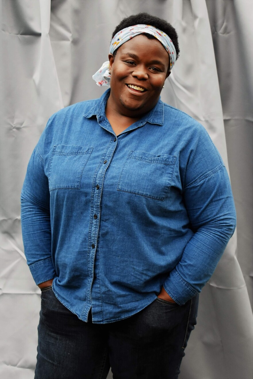 A portrait of Leah Bahan-Harris. She is smiling, wearing a denim shirt and light-colored headband.