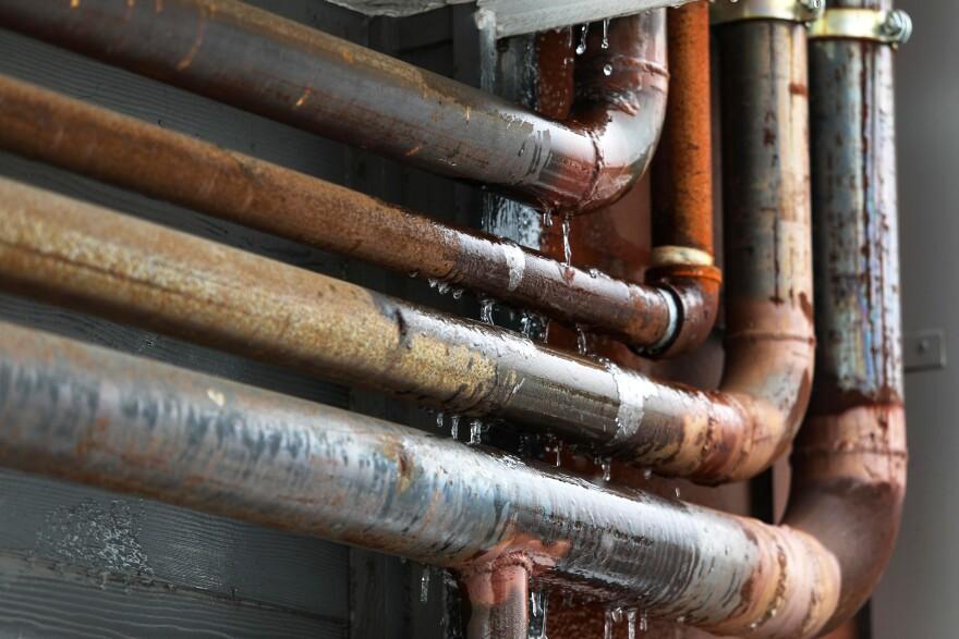 El agua se congela en las tuberías fuera de un edificio de departamentos.