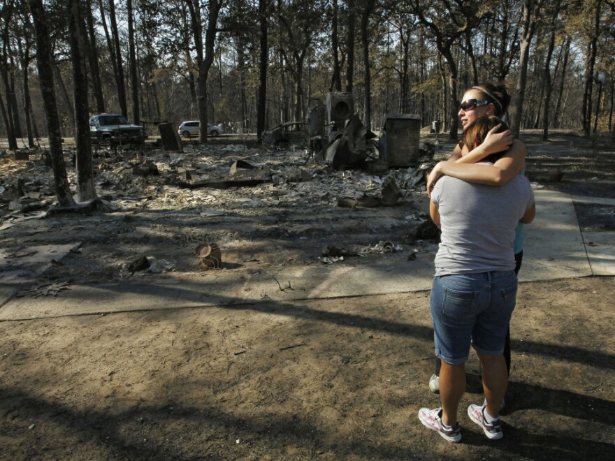 The remains of their burned home in the background, Gaye Jaco (front) hugged her stepdaughter Jennifer Leaver on Tuesday in Bastrop, Texas.