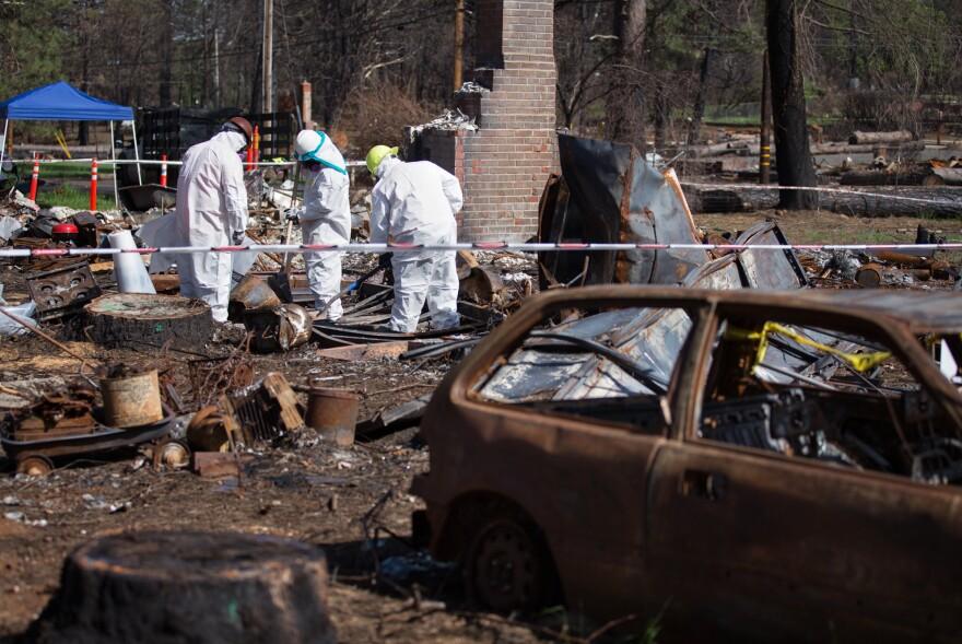Crews work to clear hazardous waste from burned properties.