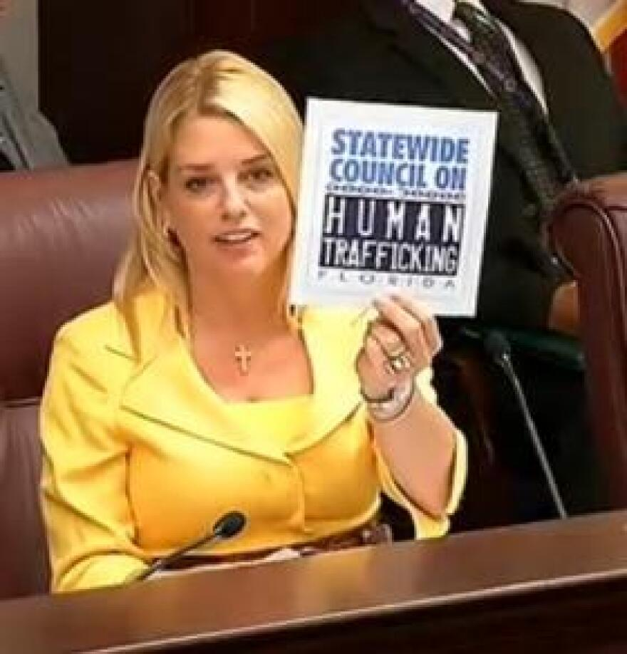 Attorney General Pam Bondi during the first meeting of the Statewide Council on Human Trafficking Monday. She's holding up the panel's new logo.