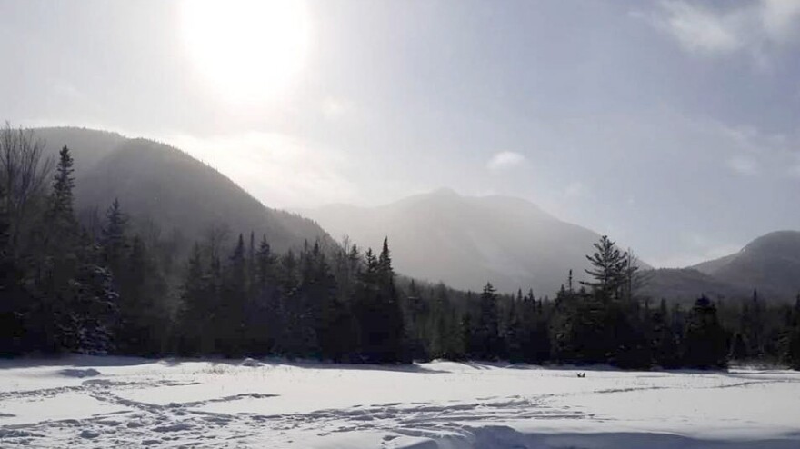 Snow dunes and an icy sun at Marcy Dam in the High Peaks of New York's Adirondack Mountains.