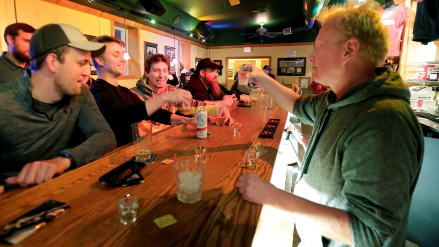 """Bar owner Michael Mattson toasts with patrons as his Friends and Neighbors bar reopens Wednesday in Appleton, Wis. Bars were able to open their doors after the Wisconsin Supreme Court struck down the state's """"Safer at Home"""" order."""